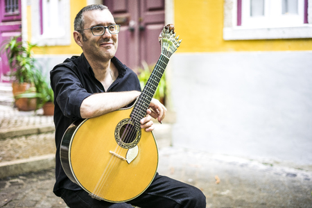 Musician with his beloved  portuguese guitar on the street of Lisbon, Portugal Imagens