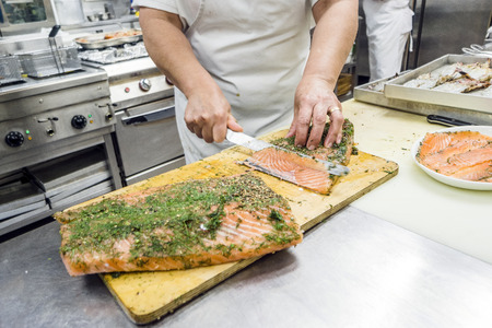 Cutting into slices a big fillet of delicious salmon in a restaurant