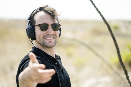Young attractive man wearing sunglasses enjoying music on his headphones