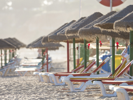 Colorful sun beds under straw umbrellas on the beach of Algarve, Portugal