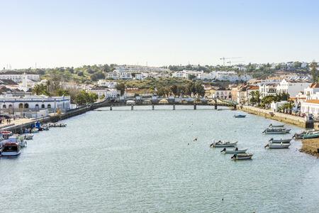 Cityscape fo Tavira with fisherman boats and roman bridge over Gilao river, Algarve, Portugal