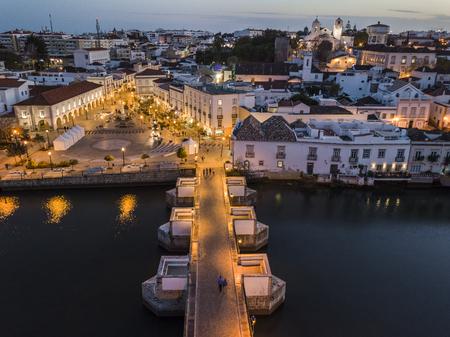 Aerial cityscape of beautiful Tavira with roman bridge over Gilao river in the evening, Algarve, Portugal