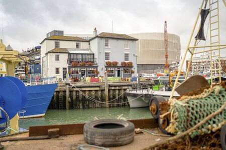 Old architecture and fisherman ships in historical dockyards of Portsmouth, Great Britain