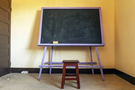 Classic blackboard with a wooden chair in a yellow classroom in Africa Imagens