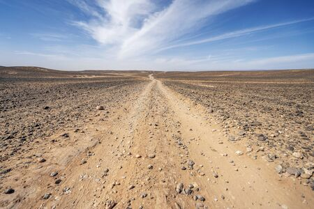 Dirt, long road through endless Sahara desert, Morocco, Africa
