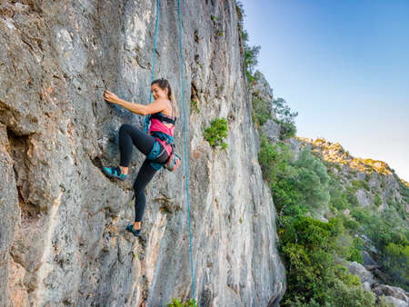 A woman in harness climbing a steep rock in Portugal