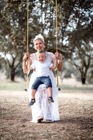 Pregnant woman having fun with her toddler son on the swing in the park