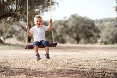 Cute happy blond toddler on the swing 免版税图像