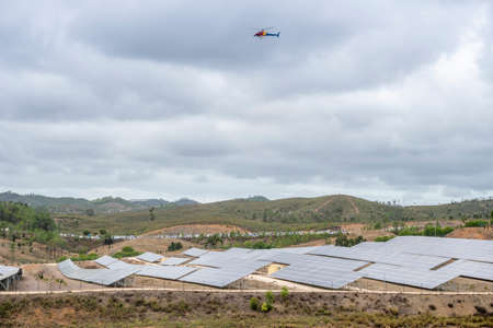 Helicopter with filming equipment over solar panels, Portugal