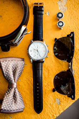 Accessories of an elegant man indluding watch, cuff links, sun glasses, belt and bow tie