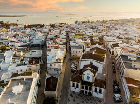 Aerial view of Olhao with a church in the foreground by sunset, Algarve, Portugal