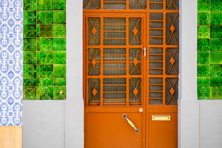Metal doors to typical fisherman's house covered with tiles called azulejo, Olhao, Algarve, Portugal