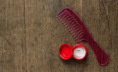 hair gel: Pink comb and hair gel on wood floor