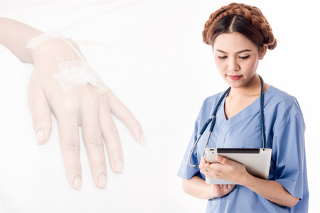 women doctor holding tablet with Women give saline solution back ground Stock Photo