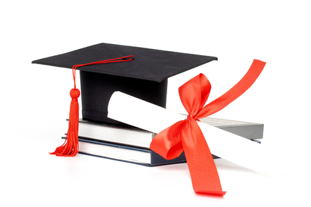 Graduation hat, book and diploma isolated on white background
