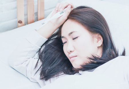 Asian woman sick sleep on  white pillow on bed in bedroom in holiday.