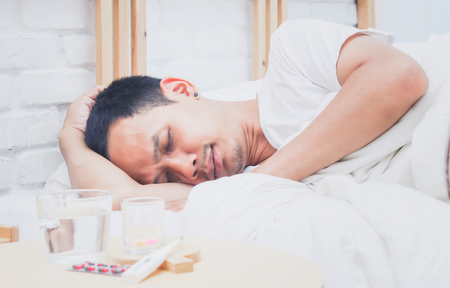 Asian man sick and sleep on bed in bedroom Banco de Imagens