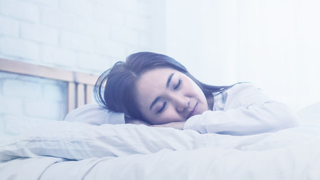 Asian woman sleep on  white pillow on bed in bedroom in holiday.happy relax time 写真素材