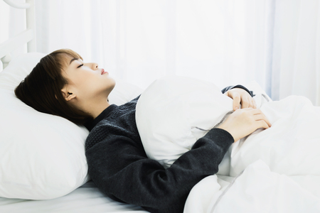 Asian woman sleep on  white pillow on bed in bedroom in holiday.happy relax time. Standard-Bild
