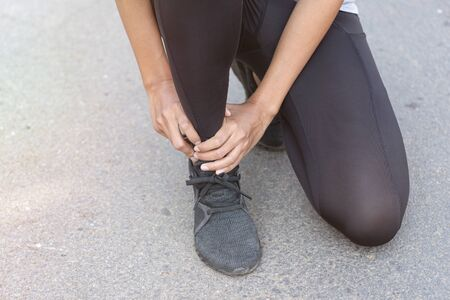 Close up Athlete running woman use hands hold on his ankle while running in the morning.Ankle injury on woman after traning for warm up her muscle.