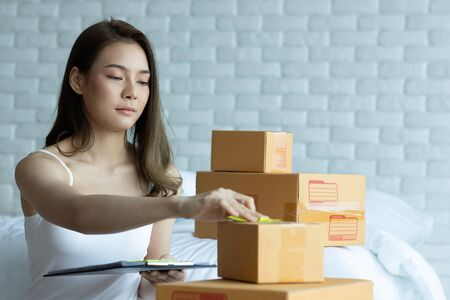 Asian women working with laptop for Online shopping at home with box for packaging in home,Own Small Business Start up for Online shopping.Small business concept.