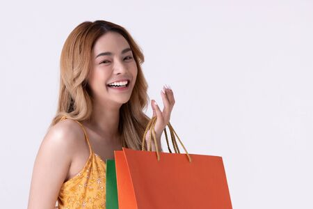 Happy asian woman holding shopping bag with mid year sale. Фото со стока