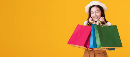 Happy asian woman holding shopping bag with mid year sale. Stock Photo