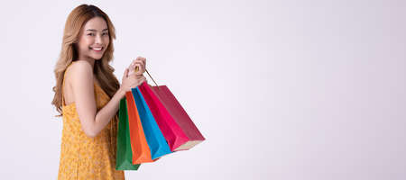 Happy asian woman holding shopping bag with mid year sale.