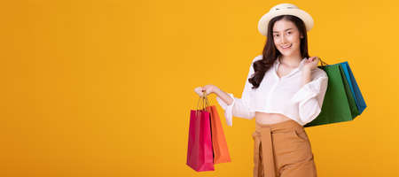 Happy asian woman holding shopping bag with mid year sale. Reklamní fotografie