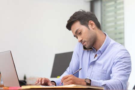 Business asian man happy working job on laptop in office. Banco de Imagens