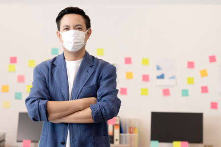 Business asian man stand and wear masks and cross arm in the office.
