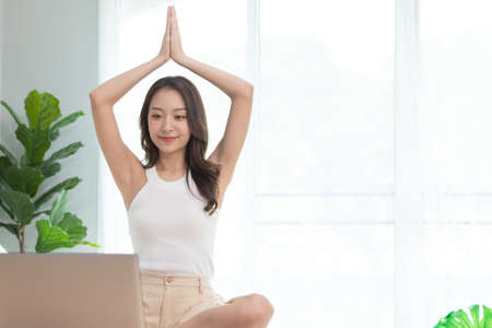 Asian woman play and learn yoga online in labtop at home. Stok Fotoğraf