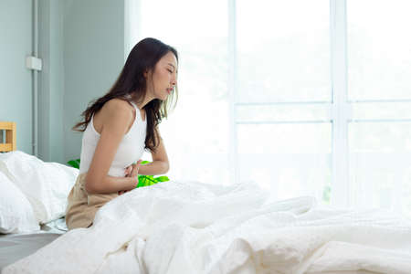 Attractive Asian woman sitting on bed have a bladder pain. Stok Fotoğraf