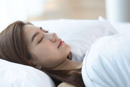 Asian women sleeping and sweet dream on white bed in bedroom Imagens