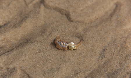 A gold ring with the head of a tiger holding a nugget in its mouth lies on the sand under the sea. Water shot close-up. Jewelry in nature