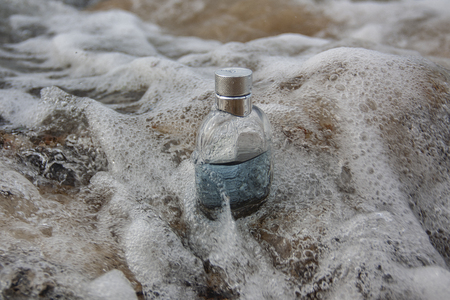 Perfume bottle in sea foam at the water's edge. Close-up shot Stock Photo