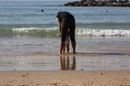 The mother supports her baby, which comes into the water for the first time. The action takes place on the beach.