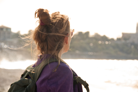 Portrait of a female tourist looking at the city in the distance as a symbol of adventure and discovery of the unknown Tourist is her back to the viewer in casual clothes with a backpack on his shoulders blured close-up against backlight.