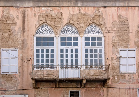 old wall of an ancient house with arched windows and balcony Фото со стока