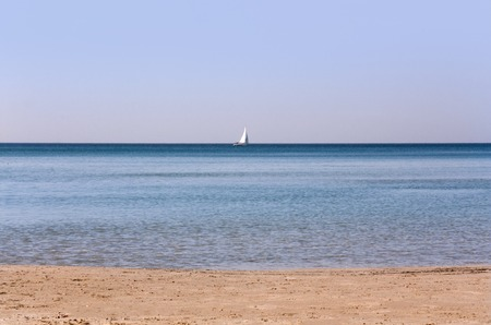 morning seascape with sailboat on the horizon as background