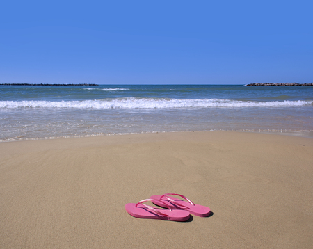 pink flip-flops on yellow sand at the edge of the sea as an invitation to go on vacation