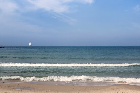 morning seascape with sailboat in the distance