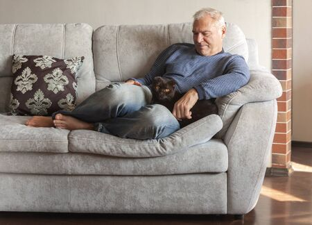 man with his favorite cat on the couch