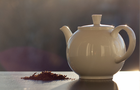 white ceramic teapot and a slide of dried tea leaves in the sunrise