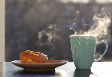 A Cup of hot steaming tea and a light custard cake by the open window in the early morning sunlight.