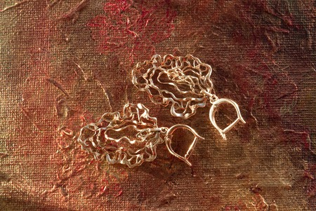 Gold openwork earrings on a picturesque terracotta background