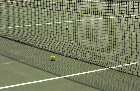 part of tennis court with net and balls