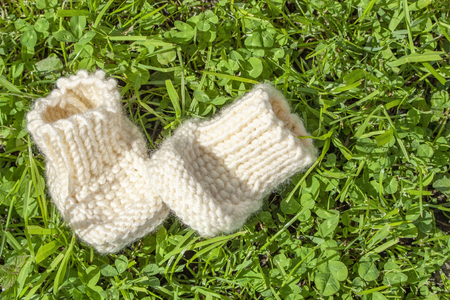 baby knitted booties on grass background close-up