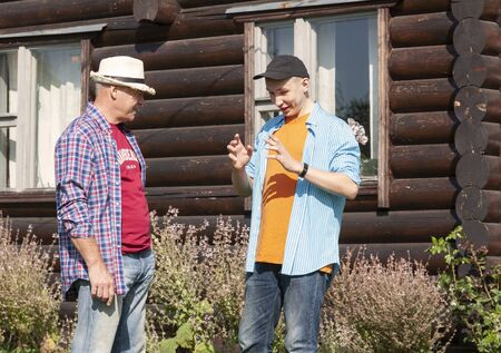 A guy and a mature man talking on the background of a log house