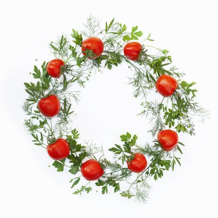 Wreath made of fresh tomato and greens as a frame